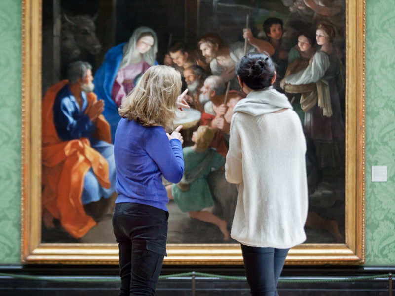 Visitors looking at a painting in the National Gallery